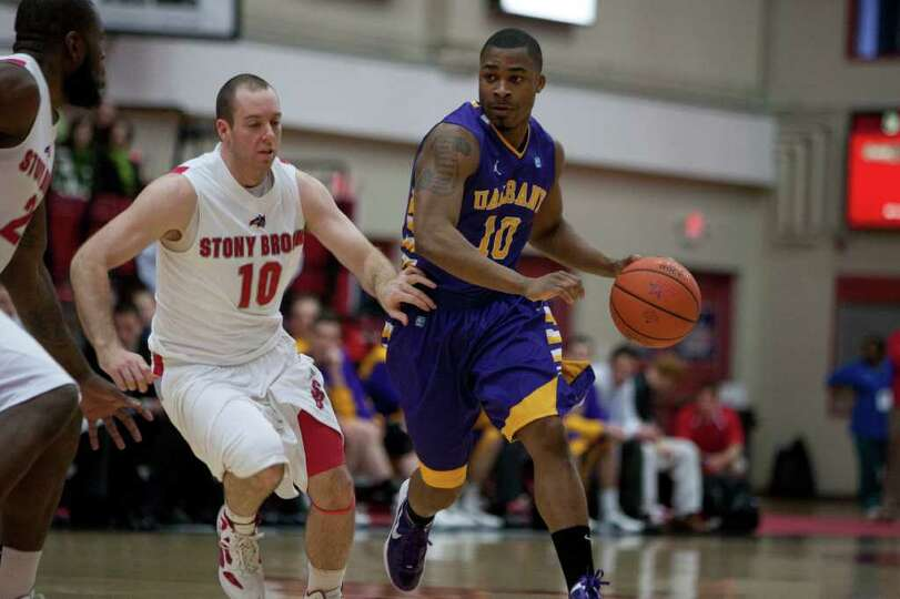Mike Black of UAlbany runs the offense as he is defended by Bryan Dougher of Stony Brook, during the