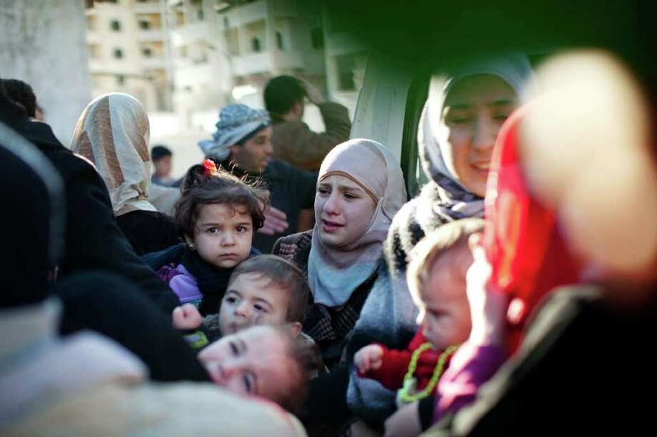 A family leaves their house in Idlib, Syria, on Sunday after it was hit by a tank. Photo: Rodrigo Abd / AP