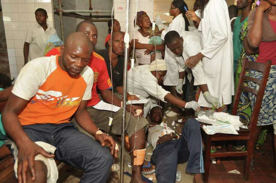 Injured people are treated by health workers at a hospital, after multiple explosions occurred at a munitions depot, in Brazzaville, Republic of Congo, Sunday, March 4, 2012.  Blasts rocked the capital of the Republic of Congo Sunday morning after a weapons depot caught fire, officials said, killing more than 200, wounding unknown numbers, and forcing some 2,000 people to flee their homes.(AP Photo/Elie Mbena) Photo: Elie Mbena / AP
