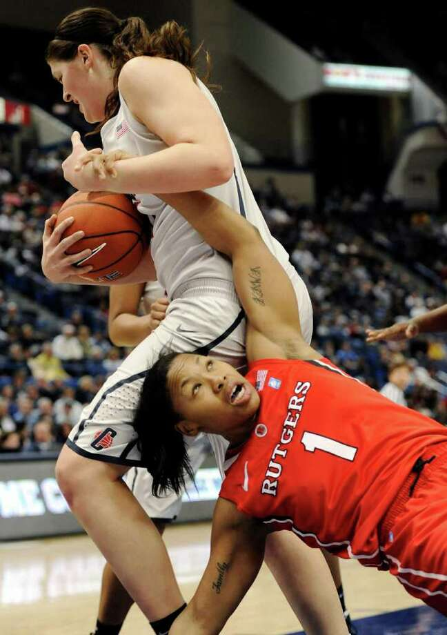 Rutgers' Khadijah Rushdan (1) fouls Connecticut's Stefanie Dolson, left, in the first half of an NCAA college basketball game in the quarterfinals of the Big East women's tournament in Hartford, Conn., Sunday, March 4, 2012. (AP Photo/Jessica Hill) Photo: Jessica Hill, Associated Press / AP2012