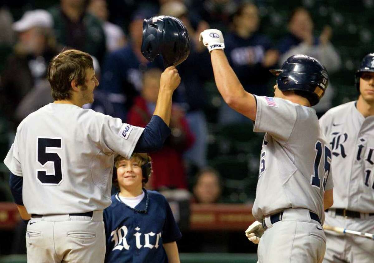 Rice University's Christian Stringer, left, congratulates Michael Fuda, center, after he hit a home run in the eighth inning of a baseball game against the University of Tennessee during the Houston College Classic at Minute Maid Park Sunday, March 4, 2012, in Houston.