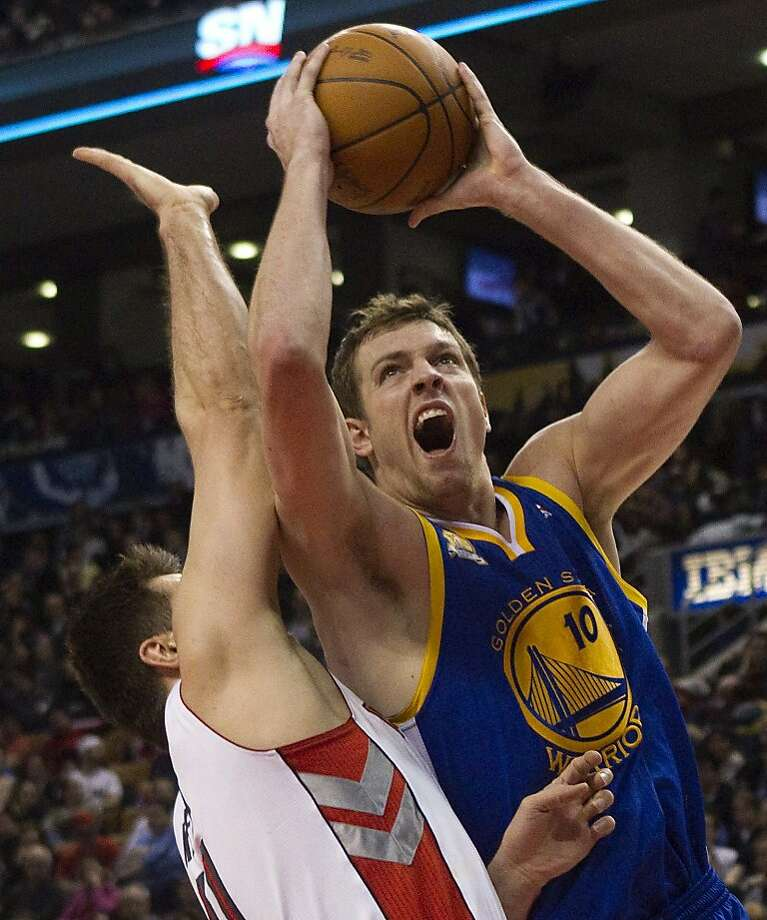 Golden State Warriors' David Lee, right, scores on Toronto Raptors' Linas Kleiza during the first half of an NBA basketball game in Toronto on Sunday, March 4, 2012. (AP Photo/The Canadian Press, Chris Young) Photo: Chris Young, Associated Press