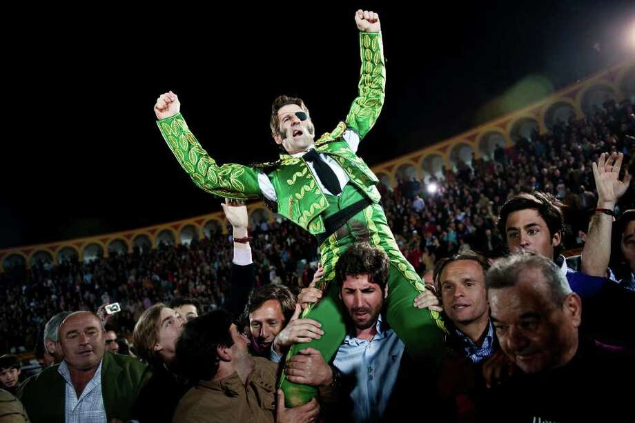 Juan Jose Padilla is carried out of the ring on the shoulders of fellow bullfighter Serafin Marin, a rare salute for only the best performers, after a bullfight Sunday. Photo: Daniel Ochoa De Olza / AP