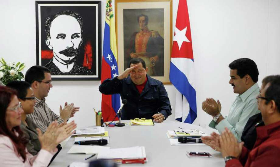 In this photo released by Miraflores Press Office Sunday March 4, 2012, Venezuela's President Hugo Chavez, center, salutes various government ministers during a televised speech at an undisclosed location in Havana, Cuba, Saturday March 3, 2012. Chavez appeared Sunday on television for the first time in nine days during which he underwent surgery in Cuba to remove a tumor. Chavez spoke firmly in footage recorded Saturday in Havana. The framed images hanging on the wall behind Chavez are of Venezuela's independence hero Simon Bolivar, right, and Cuban national hero and poet Jose Marti, left. (AP Photo/Miraflores Press Office, Marcelo Garcia) Photo: Marcelo Garcia / AP