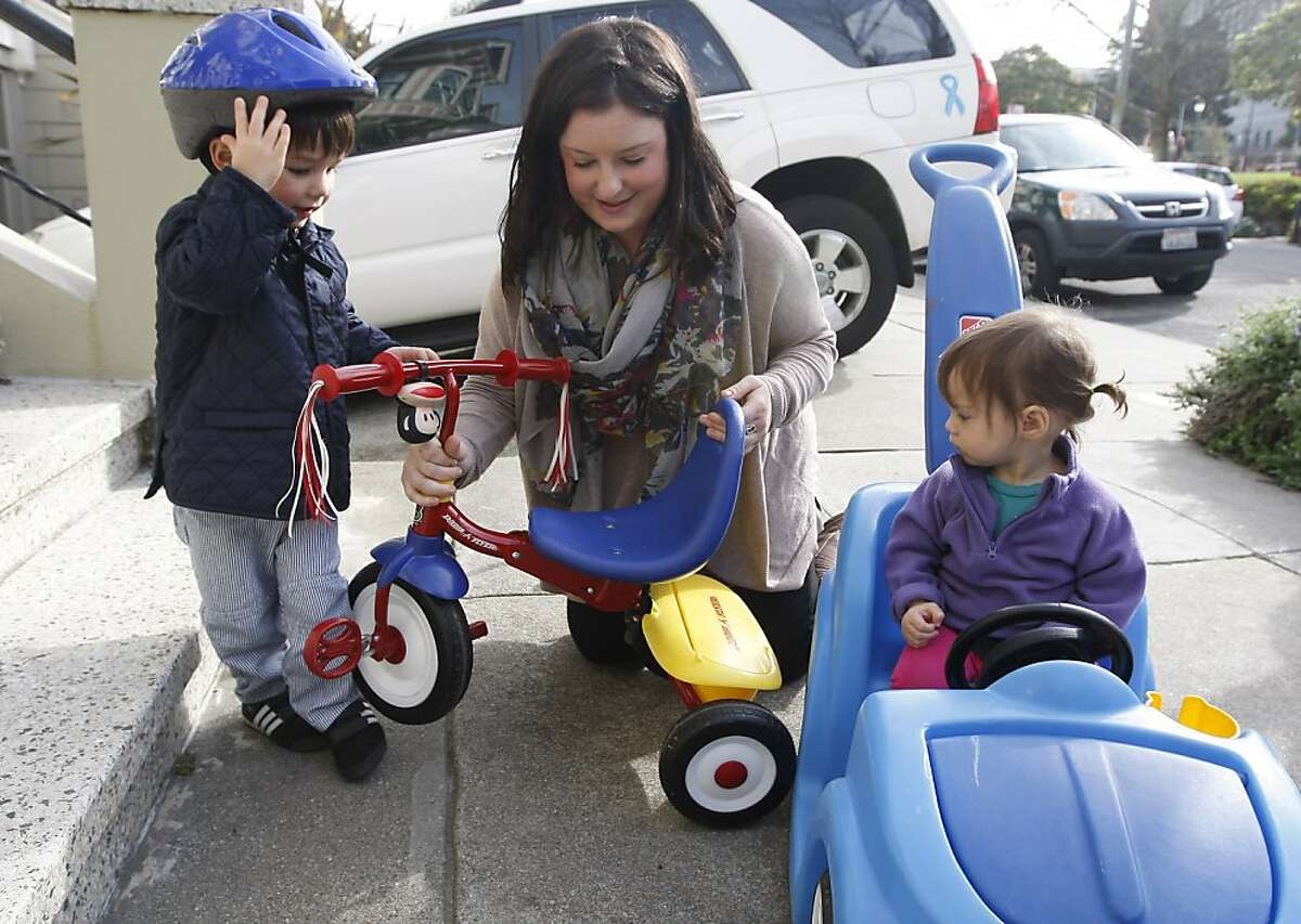Babysitter, Leanna Bullen, helps Hank Wilson (left), 3 years old, and Olive Wilson, 14 months old, as they get ready to ride bikes on Wednesday, February 29, 2012. UrbanSitter is a website that helps parents find and book babysitters throughout the city.