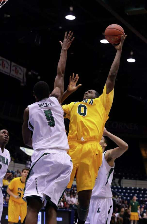 3/4/12 MassMutual Center, Springfield - Republican staff photo by Michael Beswick - The MAAC Semi-Finals were held at the MassMutual Center in Springfield Sunday.  Trying to reach the finals is New York's Siena and Maryland's Loyola.  Here, Siena's (0) Brandon Walters puts up two over Loyola's (5) Shane Walker in first half action.
