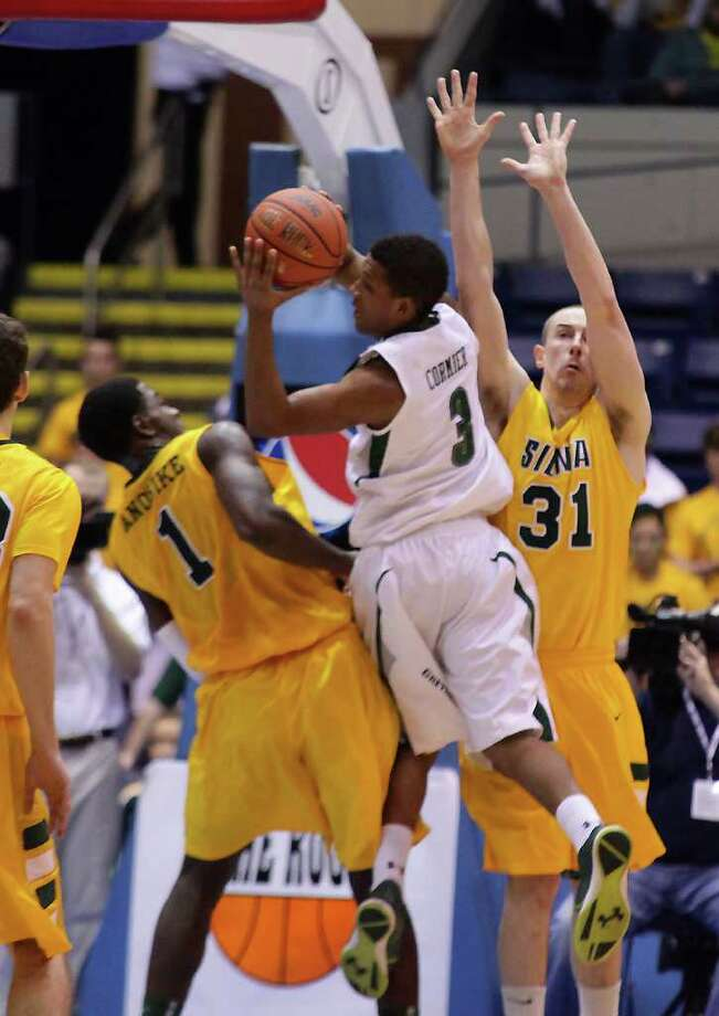 3/4/12 MassMutual Center, Springfield - Republican staff photo by Michael Beswick - The MAAC Semi-Finals were held at the MassMutual Center in Springfield Sunday.  Trying to reach the finals is New York's Siena and Maryland's Loyola.  Here, Siena's (0) Brandon Walters puts up two over Loyola's (3) Dylon Cormier heads in for two but is blocked by Siena's (1) OD Anoskie and (31) Owen Wignot.