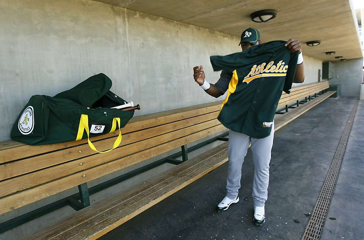 Yoenis Cespedes slips on a pratice jersey before his first workout at the Oakland A's camp in Phoenix, Ariz. on Sunday, March 4, 2012. Cespedes, who defected from Cuba last year, signed a four-year contract with Oakland.