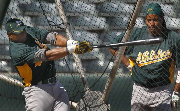 Yoenis Cespedes takes batting practice under the watchful eye of Manny Ramirez at the Oakland A's camp in Phoenix, Ariz. on Sunday, March 4, 2012. Cespedes, who defected from Cuba last year, signed a four-year contract with Oakland. Photo: Paul Chinn, The Chronicle