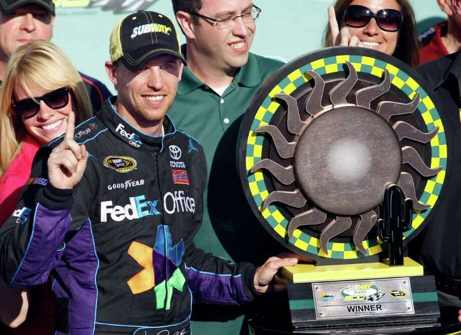 Denny Hamlin stands next to the trophy after winning the NASCAR Sprint Cup Series auto race at Phoenix International Raceway on Sunday, March 4, 2012, in Avondale, Ariz. (AP Photo/Paul Connors) Photo: Paul Connors