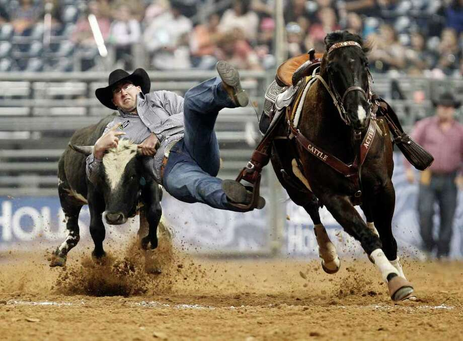 Cole Edge puts together a time of 29.7 in the steer wrestling on Sunday night. Photo: James Nielsen / © 2011 Houston Chronicle