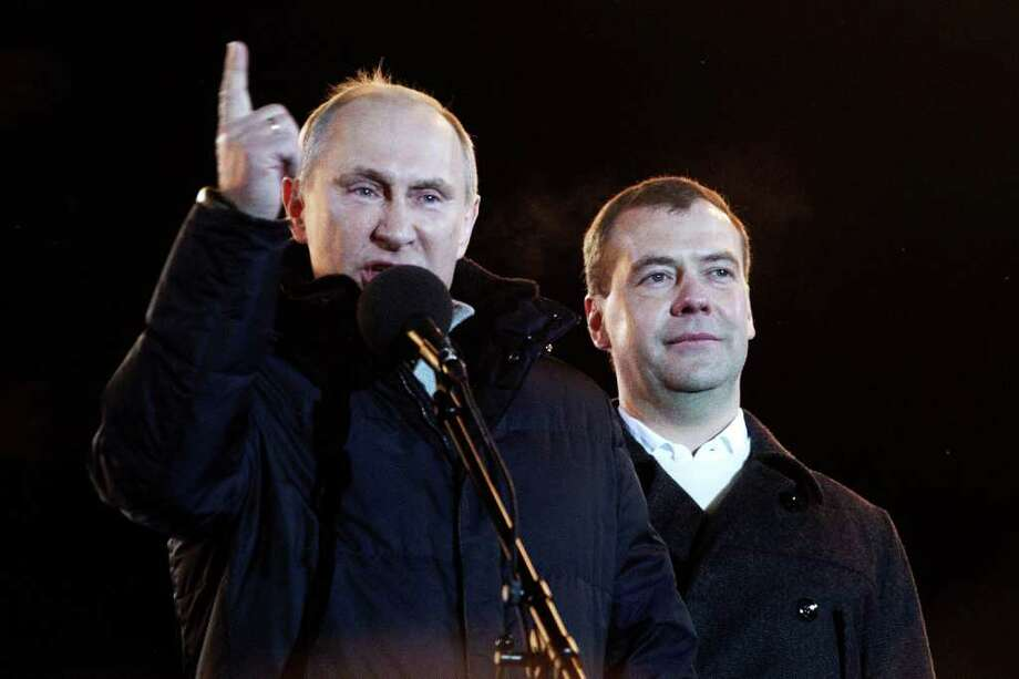 MOSCOW, RUSSIA - MARCH 4: Russian Prime Minister and presidential candidate Vladimir Putin speaks as current President Dmitry Medvedev (R) listens during a rally after Putin claimed victory in the presidential election at the Manezhnya Square March, 4, 2012 in Moscow, Russia. Exit polls showed Putin had over 58 percent of the vote according to state television in an election that has been alleged to be marred by widespread violations. (Photo by Oleg Nikishin/Epsilon/Getty Images) Photo: Oleg Nikishin