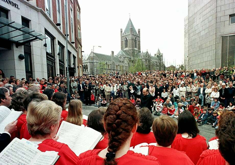 FILE- The people of Dublin gather near to Christ Church Cathedral, background, singing excerpts from Handel's Messiah in this file photo dated Sunday April 13, 1997, in Dublin, Ireland. The cathedral is a cultural heart of Dublin's fair city, but Officials at the Cathedral said Sunday March 4, 2012, that they are distraught and perplexed over the theft of the church's most precious relic, the preserved heart of St. Laurence O'Toole, patron saint of Dublin. O'Toole's heart had been displayed in the cathedral since the 13th century, but on Saturday Feb.3,  a thief cut the relic from its fixings and made off with the heart of Dublin. (AP Photo/John Cogill, File) Photo: John Cogill, Associated Press