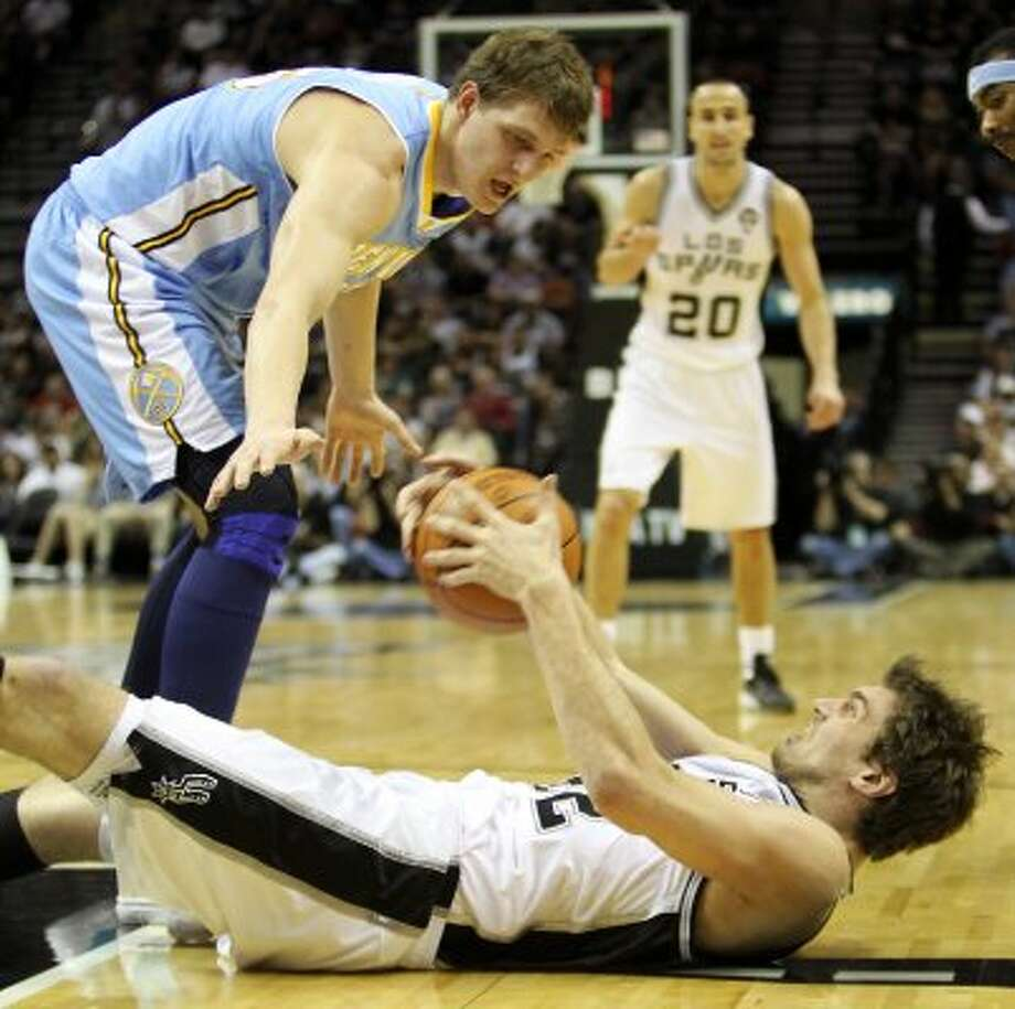 Tiago Splitter manages to maintain control and pass to Duncan after a fall guarded by Denver's Timofey Mozgov in the first half Spurs vs Nuggets, Sunday, March 4, 2012. (JENNIFER WHITNEY) (special to the Express-News)
