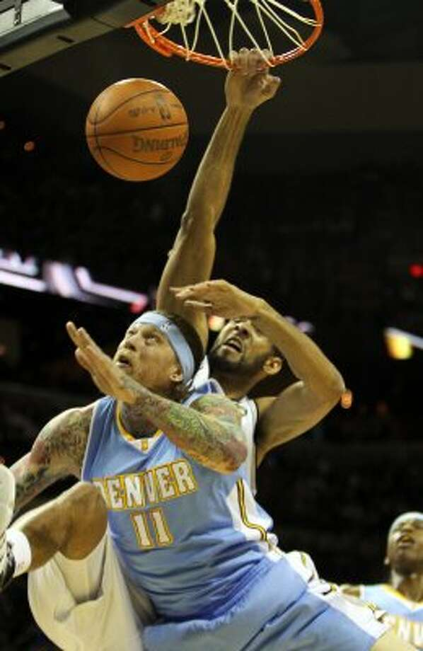 Tim Duncan gets the dunk guarded by Denver's Chris Andersen in the first half Spurs vs Nuggets, Sunday, March 4, 2012. (JENNIFER WHITNEY) (special to the Express-News)