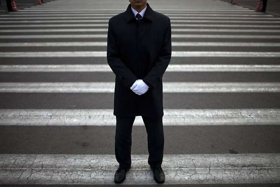 A Chinese soldier dressed as an usher guards an entrance to the the Great Hall of the People where the opening session of the annual National People's Congress is held in Beijing, China, Monday, March 5, 2012. (AP Photo/Alexander F. Yuan) Photo: Alexander F. Yuan, Associated Press