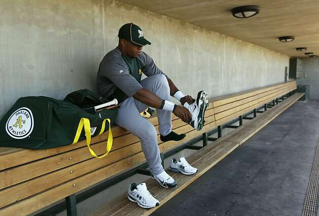 Yoenis Cespedes puts on new spikes before his first workout at the Oakland A's camp in Phoenix, Ariz. on Sunday, March 4, 2012. Cespedes, who defected from Cuba last year, signed a four-year contract with Oakland. Photo: Paul Chinn, The Chronicle
