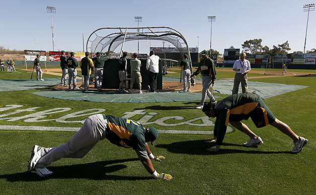 Yoenis Cespedes (left) stretches with conditioning coach Mike Henriques before his first workout at the Oakland A's camp in Phoenix, Ariz. on Sunday, March 4, 2012. Cespedes, who defected from Cuba last year, signed a four-year contract with Oakland. Photo: Paul Chinn, The Chronicle
