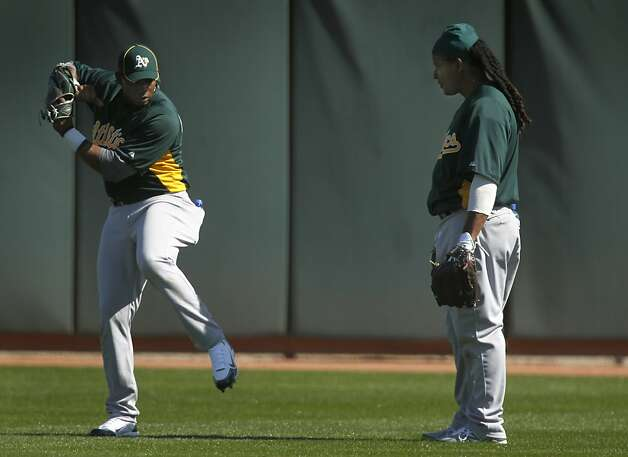 Yoenis Cespedes shows his batting stance to Manny Ramirez while shagging fly balls at the Oakland A's camp in Phoenix, Ariz. on Sunday, March 4, 2012. Cespedes, who defected from Cuba last year, signed a four-year contract with Oakland. Photo: Paul Chinn, The Chronicle
