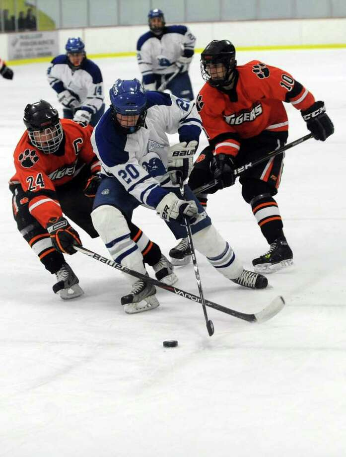Darien's Trent Bergin, center, controls the puck as he is surrounded by Ridgefield's Brendan Bossidy, left, and Henry Gough, right, during Saturday's FCIAC Teir I Boys Hockey Championship at Terry Conners Rink in Stamford on March 3, 2012. Photo: Lindsay Niegelberg / Stamford Advocate
