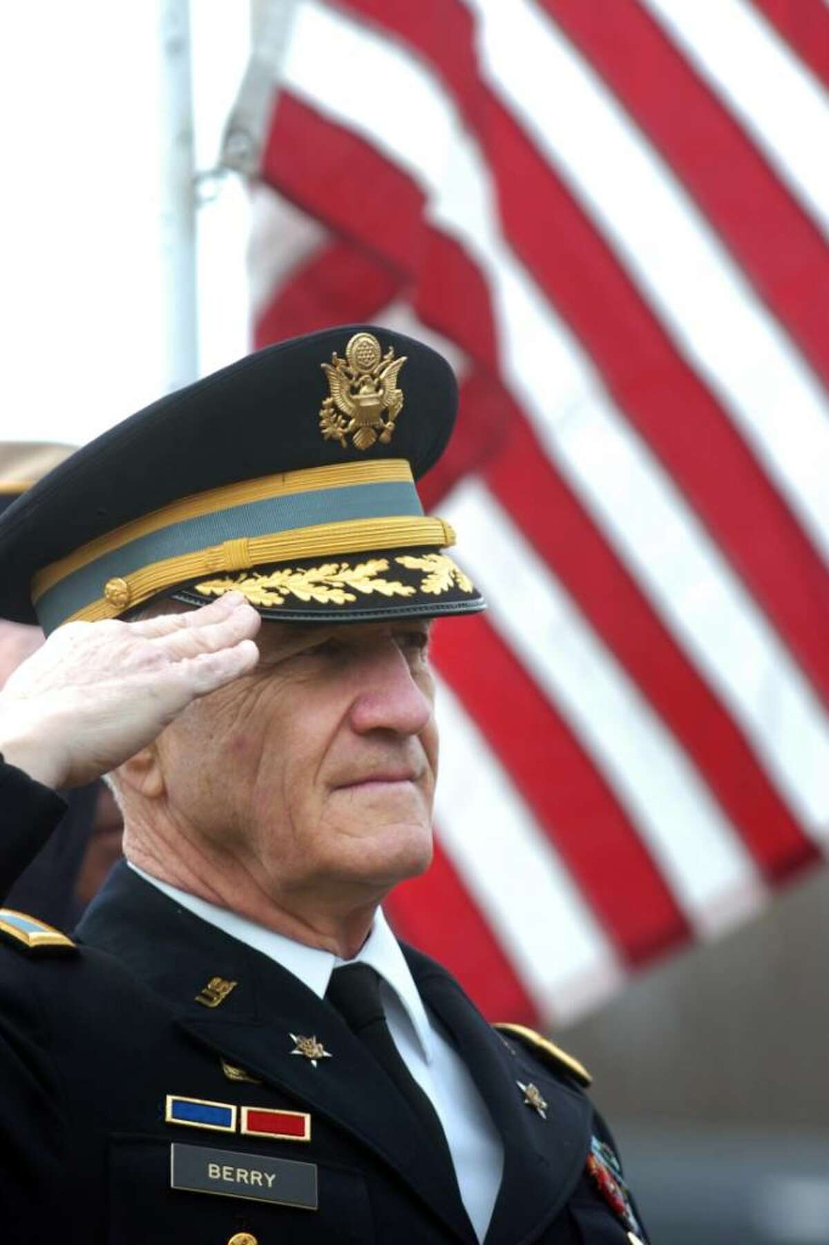 Retired U.S. Army Col. Ron Berry, of Easton, salutes as the National Anthem is played at the start of the Veterans Day ceremony on the Stepney Green, in Monroe, Conn. Wed. Nov. 11th, 2009.