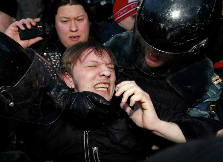 Russian police officers detain an opposition protester during a protest near the Central Election Committee in Moscow, Monday, March 5, 2012. Demonstrators are contesting the outcome of the vote, pointing to a campaign heavily slanted in Putin's favor and to reports of widespread violations in Sunday's ballot. (AP Photo/Ivan Sekretarev) Photo: Ivan Sekretarev, Associated Press / AP
