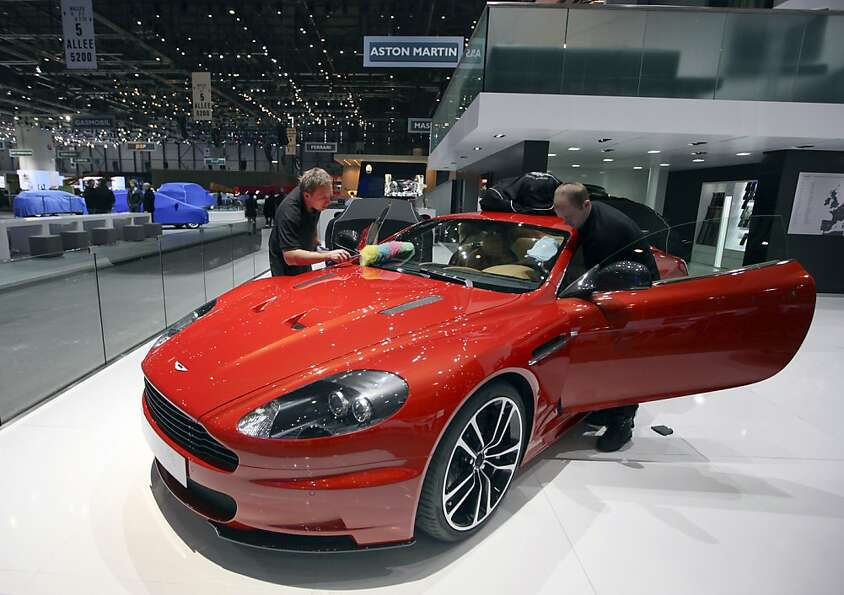 Employees work to prepare an Aston Martin DBS Coupe Carbon Edition automobile on the company's stand