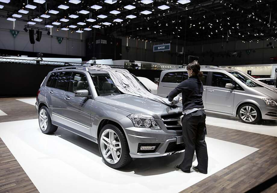 A woman adjusts the protective cover across a Mercedes-Benz CL automobile on the company's stand, ahead of the opening press day at the Geneva International Motor Show in Geneva, Switzerland, on Monday, March 5, 2012. The 82nd Geneva International Motor Show will showcase the latest models from the auto industry's leading manufacturers at the Palexpo exhibition centre this week. Photographer: Jason Alden/Bloomberg Photo: Jason Alden, Bloomberg