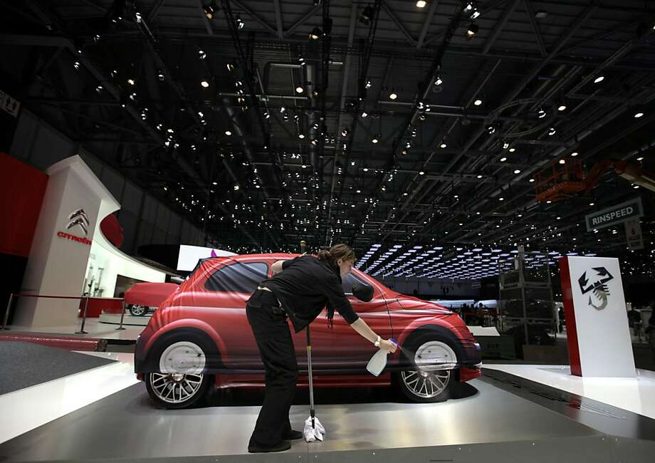 A woman uses a broom to clean the stand next to a Fiat 500 Abarth automobile, ahead of the opening press day at the Geneva International Motor Show in Geneva, Switzerland, on Monday, March 5, 2012. The 82nd Geneva International Motor Show will showcase the latest models from the auto industry's leading manufacturers at the Palexpo exhibition centre this week. Photographer: Jason Alden/Bloomberg Photo: Jason Alden, Bloomberg