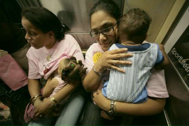 Daniele Poole-Smith, left, breastfeeds her daughter Salani, 2, while Valerie Roman cuddles her sleeping son Herbert, 8 months, while riding on a subway train in New York. (BEBETO MATTHEWS / AP)