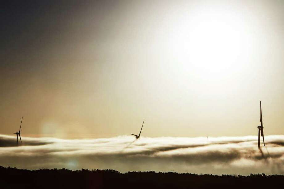 A thick cloud of fog and morning light engulfs two 285ft tall 2.5 MW Clipper wind turbines at the BP Sherbino Mesa II Wind Farm, Monday, Feb. 20, 2012, in Fort Stockton.  After cutting its solar program last year, BP is beefing up its investments into wind energy and recently launched its fourth Texas wind farm, in Fort Stockton. On 20,000 acres in Pecos County, the Sherbino II farm has 60 wind turbines to generate enough electricity to power more than 175,000 homes. Photo: Michael Paulsen, Houston Chronicle / © 2012 Houston Chronicle