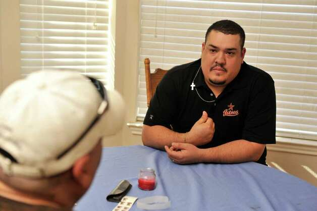 Golfer Justo Flores talks with his father Justo Flores after he was injured by a stray bullet while he was golfing on the 12th hole of the Mission Del Lago municipal course on the far south side. Photo: Robin Jerstad, For The Express-News