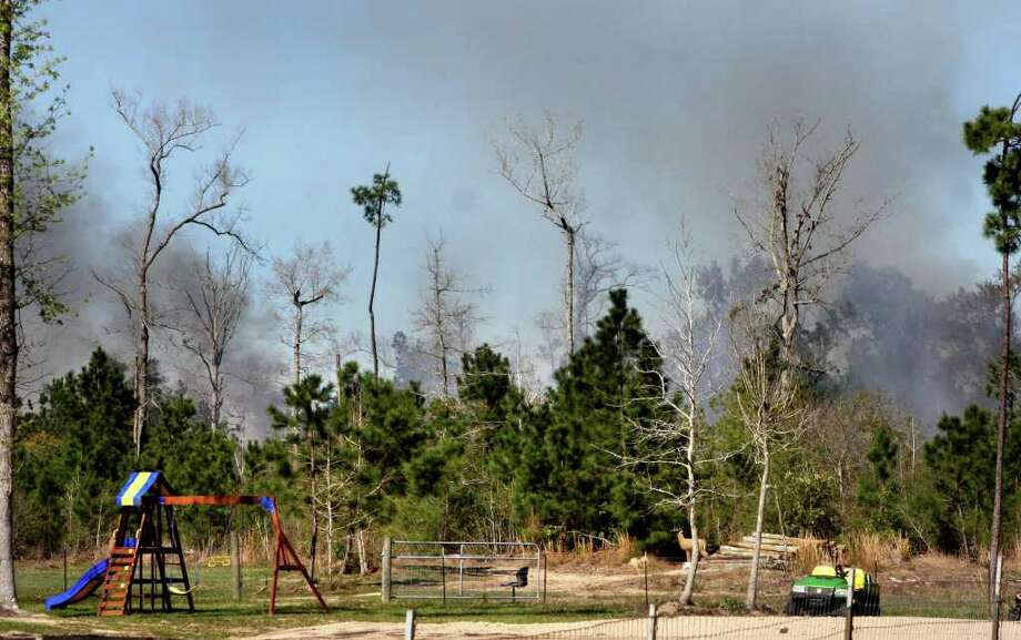 Firefighters from Emergency Services District #5, Nome VFD, Bevil Oaks VFD, and Lumberton Fire and EMS battled a 100-acre fire on Silver Star Raod in Sour Lake on Monday, March 5. By 4 p.m. the fire was 80 percent contained. Photo: David Lisenby, HCN_Fire 030512