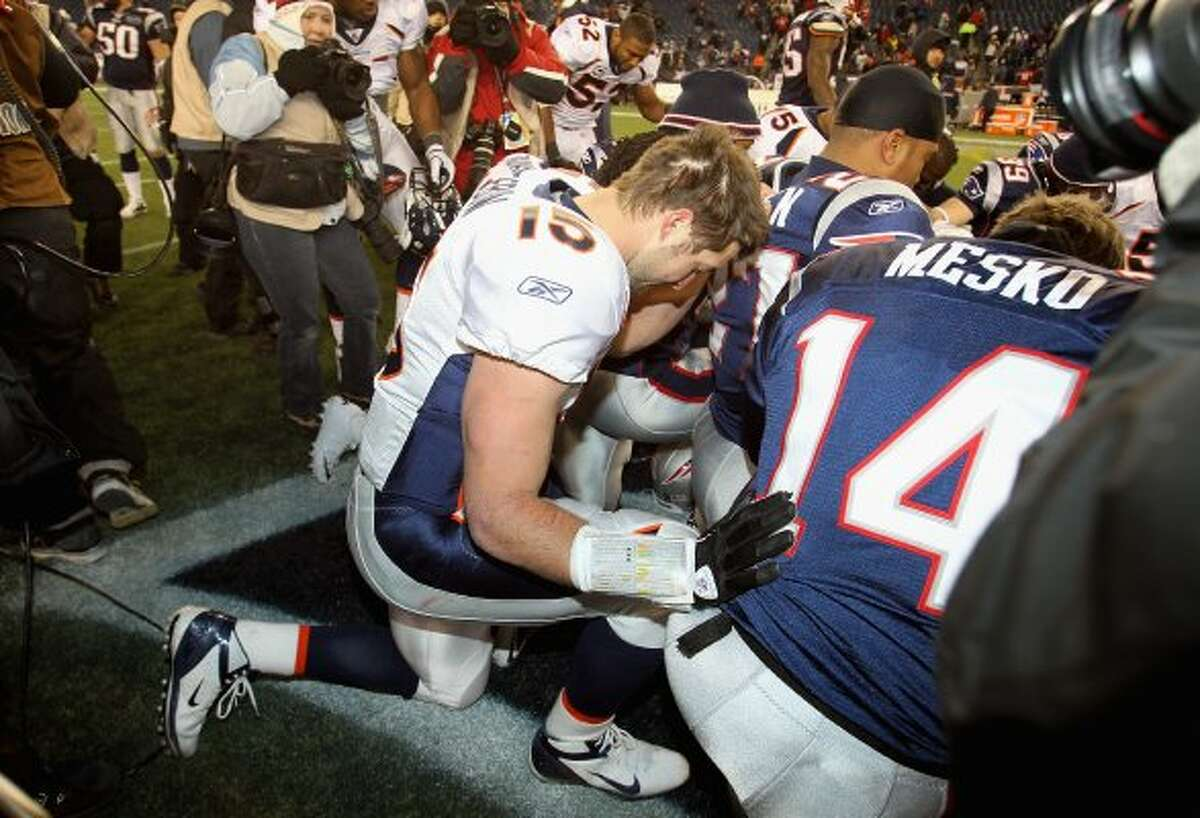 FOXBORO, MA - JANUARY 14: Tim Tebow #15 of the Denver Broncos kneels and prayers with teammates and members of the New England Patriots after the Patriots won 45-10 during their AFC Divisional Playoff Game at Gillette Stadium on January 14, 2012 in Foxboro, Massachusetts. (Photo by Jim Rogash/Getty Images) (Jim Rogash / Getty Images)