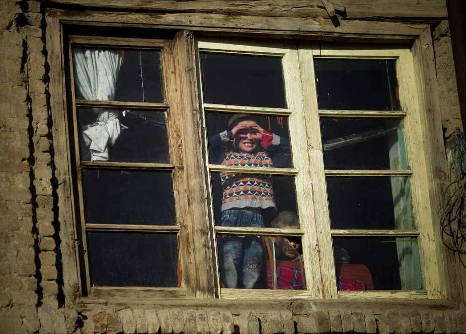 Afghan boys peer through a window in Kabul, Afghanistan, Monday, March 5, 2012. (AP Photo/Anja Niedringhaus) Photo: Anja Niedringhaus / AP