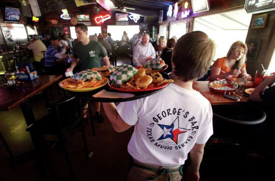 In this March 3, 2012 photo, Ben Morgan, an employee at George's restaurant delivers an order, in Waco, Texas. U.S. service companies expanded in February at the fastest pace in a year, helped by a rise in new orders and job growth. (AP Photo) Photo: Associated Press / AP