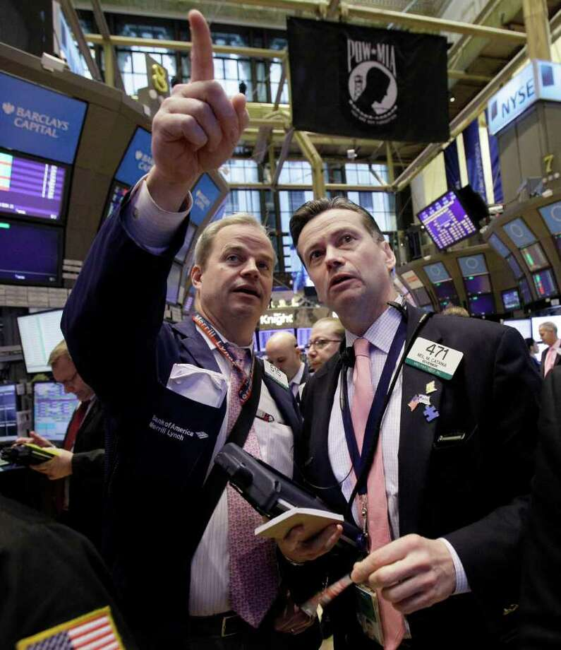 FILE - In this March 2, 2012 file photo, traders David O'Day, left, and Neil Catania confer on the floor of the New York Stock Exchange. Worries over China's economic growth and whether Greece can entice enough private creditors to participate in a bond swap deal weighed on markets Monday, March 5, 2012, at the start of a busy week which culminates with closely-watched U.S. jobs figures. (AP Photo/Richard Drew, File) Photo: Richard Drew