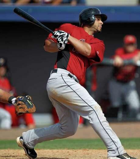 The Astros' Fernando Martinez follows through on a three-run homer off Nationals pitcher Tom Gorzelanny in the fourth inning Sunday. Photo: Julio Cortez / AP