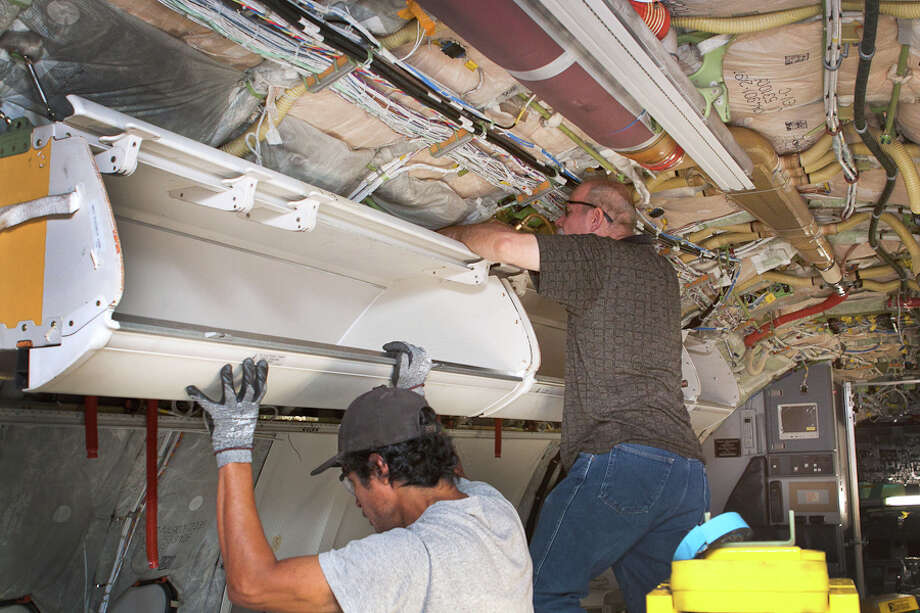 This undated photo provided by American Airlines parent company AMR, shows workers installing larger bins for carry-on luggage on a Boeing 737, in Tulsa, Okla. Fliers can stop sharpening their elbows. Overhead bins are getting bigger. (AP Photo/AMR) Photo: Byron Totty