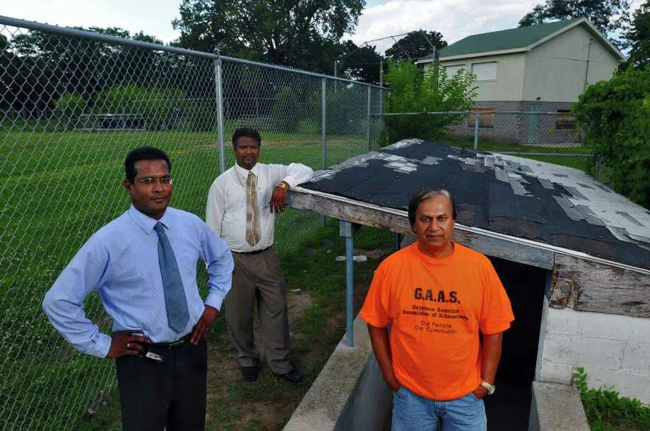 Leakh Bhoge, (Treasurer), right,  Bhisham Nandalall (Vice President), center, and John Mootooveren, (President), left,  of the Guyanese American Association of Schenectady want to build a state of the art cricket field and a facility to host cultural events for the community at Grout Park in Schenectady, NY, seen here in the first base dugout of the old baseball field on Wednesday August 12, 2009.  They are working with the city and the county and have already secured some funding for the project. For a long time, the park was abandoned. FOR PAUL NELSON STORY. (Philip Kamrass  /  Times Union) Photo: PHILIP KAMRASS / 00005071A