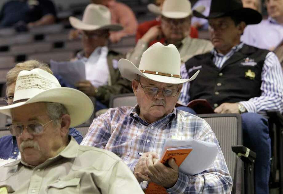 Ken O'Rear of Houston keeps track of sales information during the bull sale in the Reliant Arena sales pavilion. He bought one bull for his San Saba ranch. Photo: Melissa Phillip / © 2012 Houston Chronicle