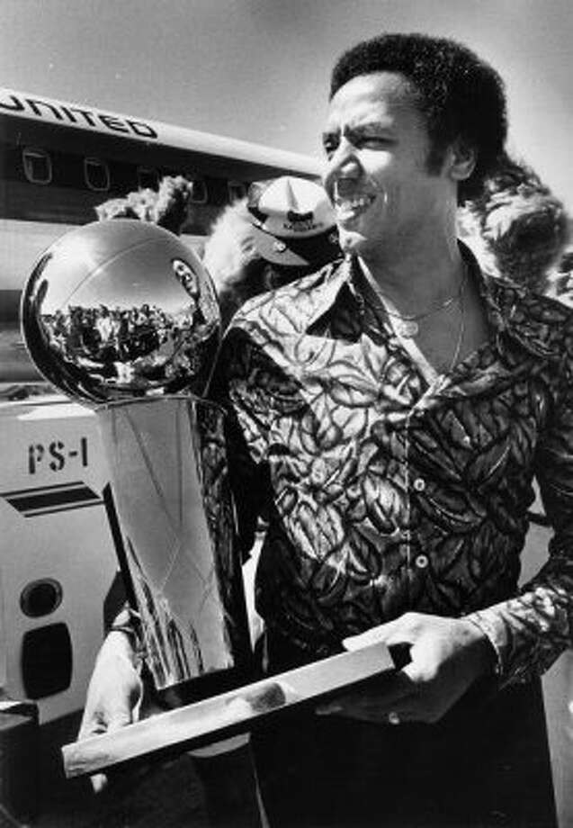 Coach Lenny Wilkens carries the 1979 NBA championship trophy after a flight back from Washington D.C., where the Sonics won it by beating the Bullets.