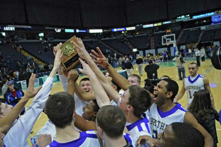 CBA players Sully Crotty holds up the Section II Class AA championship plaque as he celebrates with teammates after the end of their 62-57 overtime victory over Troy High School in the Section II Class AA boys basketball final at the Times Union Center on Monday night March 5, 2012 in Albany, N.Y. CBA won their fourth straight Section II crown, and were in the finals for the 10th straight time. (Philip Kamrass / Times Union ) Photo: Philip Kamrass / 00016679A