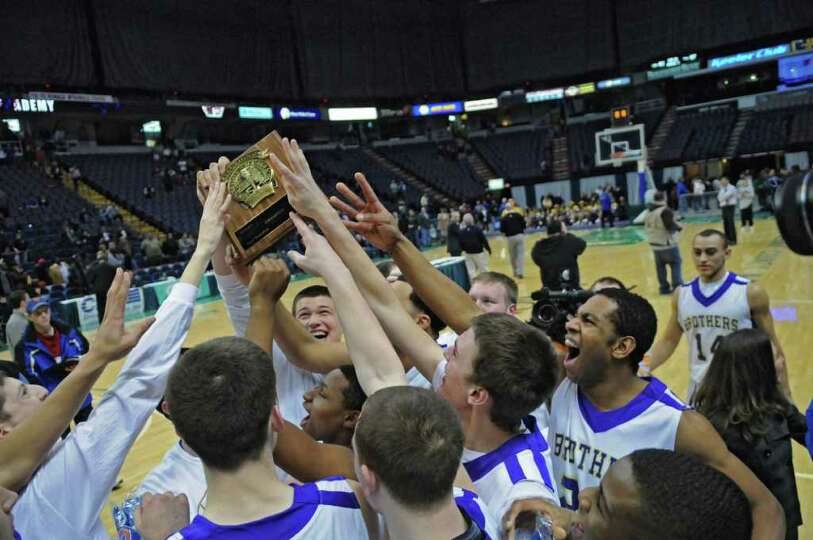 CBA players Sully Crotty holds up the Section II Class AA championship plaque as he celebrates with