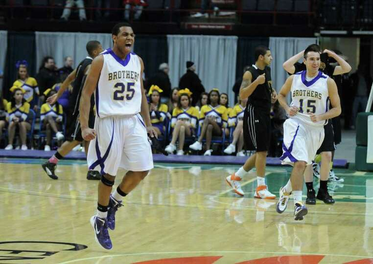 CBA players Earl Ricketts, left, and Joe Krong, right, celebrate after the end of their 62-57 overti
