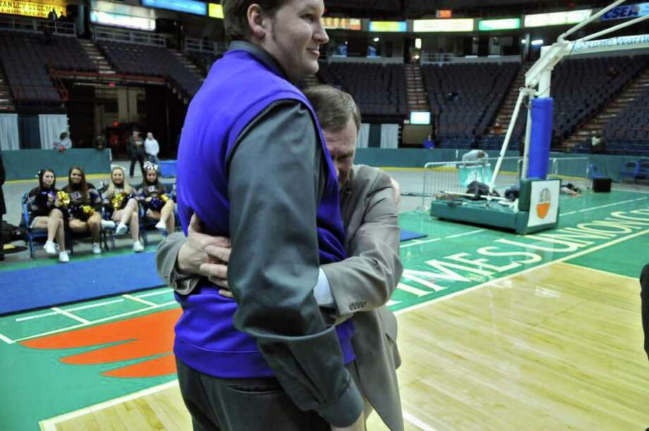 CBA boys basketball head coach Dave Doemel, right, hugs assistant coach Josh Duell, left, after CBA's 62-57 overtime victory over Troy High School in the Section II Class AA boys basketball final at the Times Union Center on Monday night March 5, 2012 in Albany, N.Y. CBA won their fourth straight Section II crown, and were in the finals for the 10th straight time. Duell played basketball for both CBA and Siena. (Philip Kamrass / Times Union ) Photo: Philip Kamrass / 00016679A