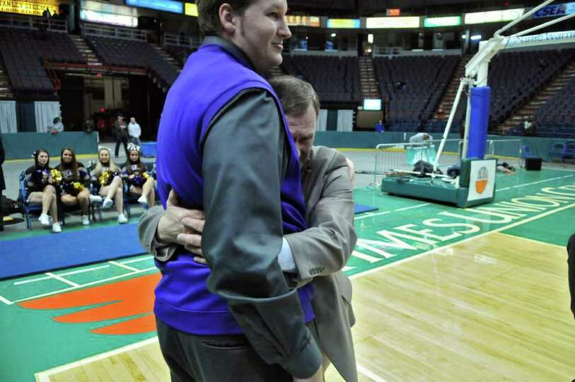 CBA boys basketball head coach Dave Doemel, right, hugs assistant coach Josh Duell, left, after CBA'