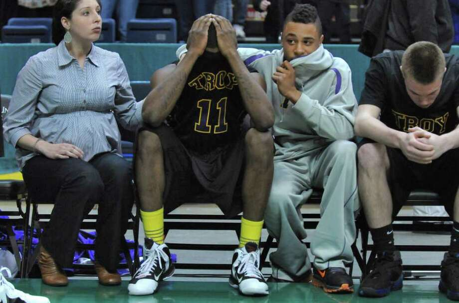 Troy's Trahmier Burrell, #11, is comforted on the bench after their 62-57 overtime loss to CBA in the Section II Class AA boys basketball final at the Times Union Center on Monday night March 5, 2012 in Albany, N.Y. CBA won their fourth straight Section II crown, and were in the finals for the 10th straight time. Duell played basketball for both CBA and Siena. (Philip Kamrass / Times Union ) Photo: Philip Kamrass / 00016679A