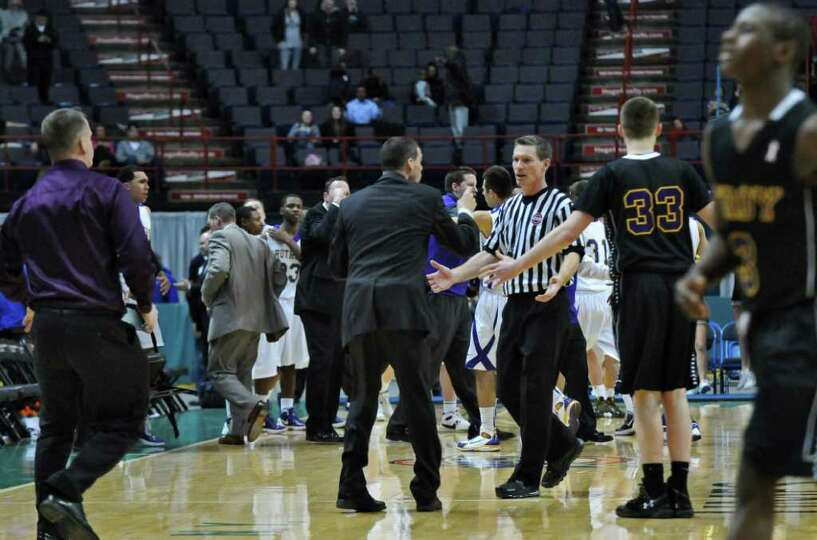 Troy coach Richard Hurley talks to an official on the court at the end of regulation of their 62-57
