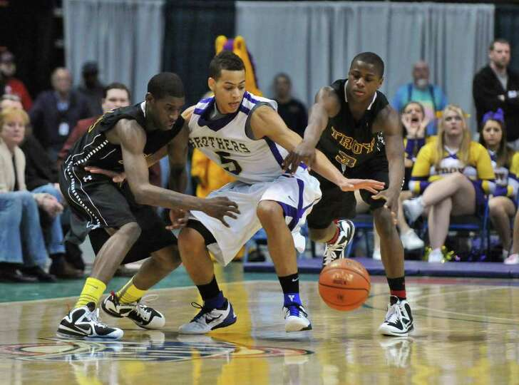 Troy's Trahmier Burrell, left, and Dyaire Holt, right, defend CBA's Christian Leppanen, center,  on